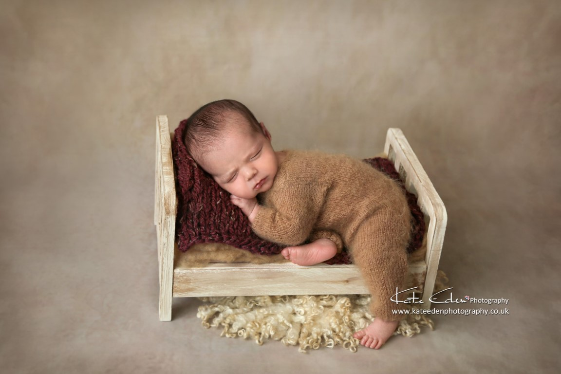 Newborn baby in a mini bed - Kate Eden Photography