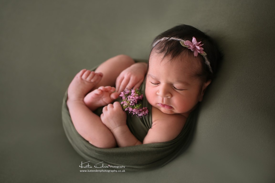 Beautiful newborn baby girl with violet heather in green - Kate Eden Photography - Milton Keynes