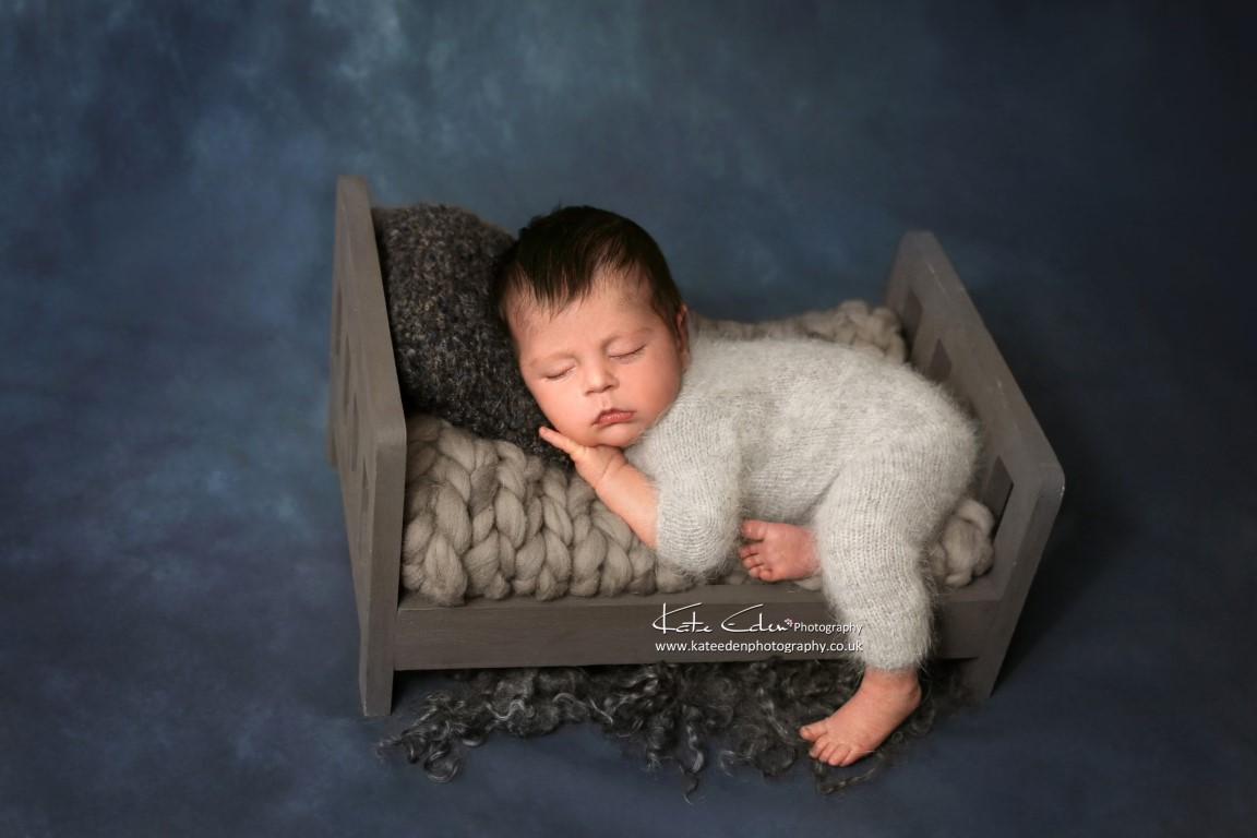 A newborn baby boy in mini-bed - Kate Eden Photography - Milton Keynes newborn photographer
