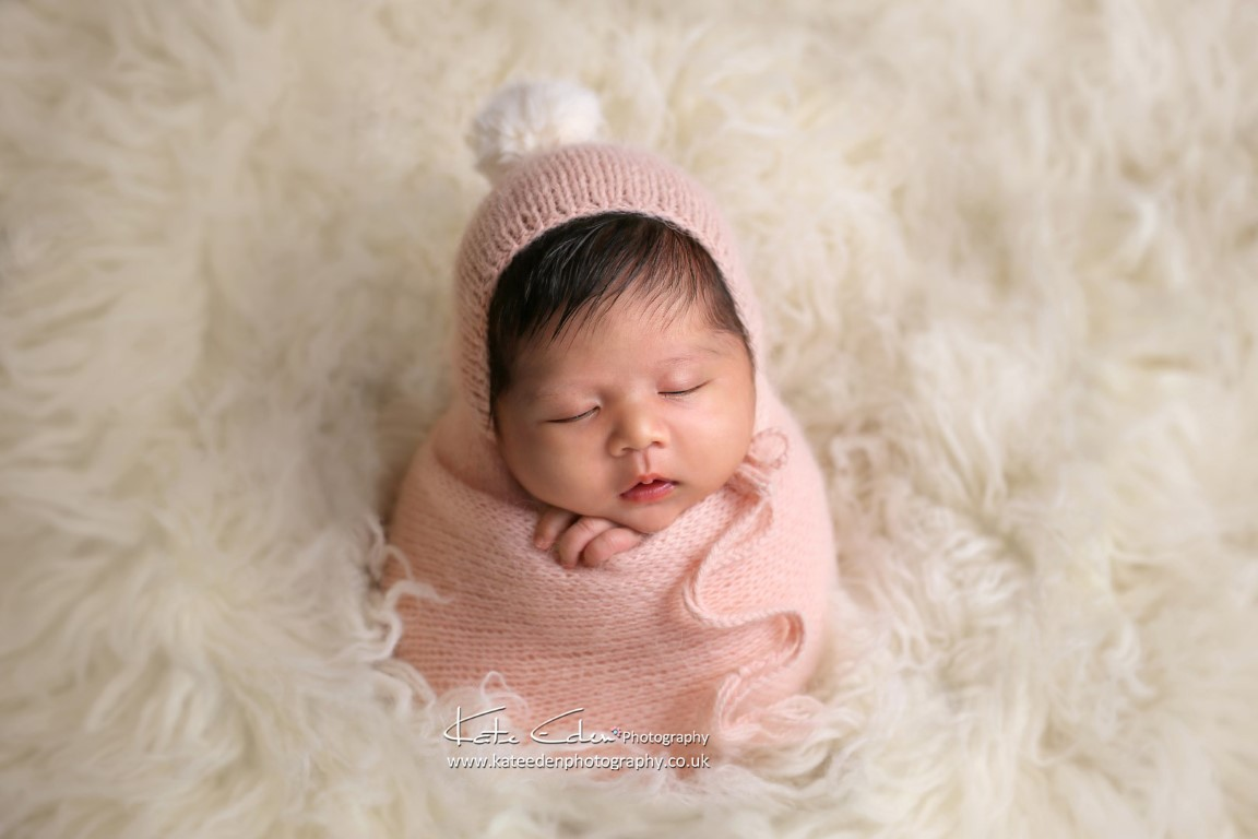 Newborn baby girl in pom-pom hat - Kate Eden Photography - newborn photographer