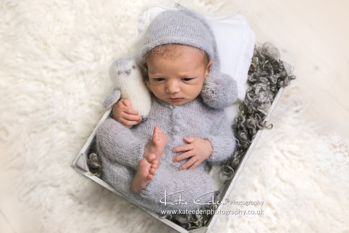 newborn baby boy in grey overall with a penguin and pom-pom hat / newborn photography Aberdeen