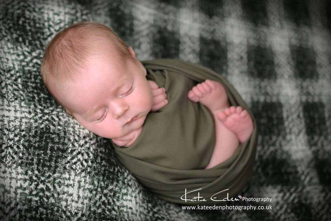 Adorable newborn baby boy on green plaid