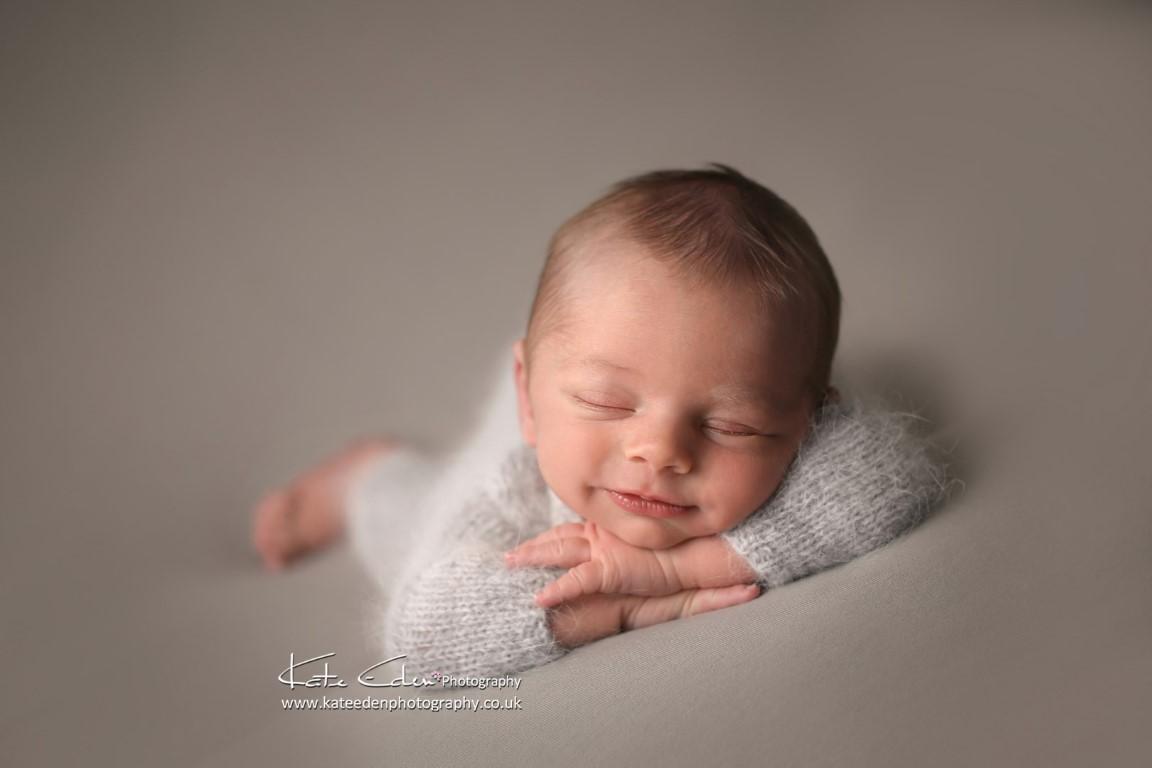 Happy newborn baby boy in grey - Kate Eden Photography