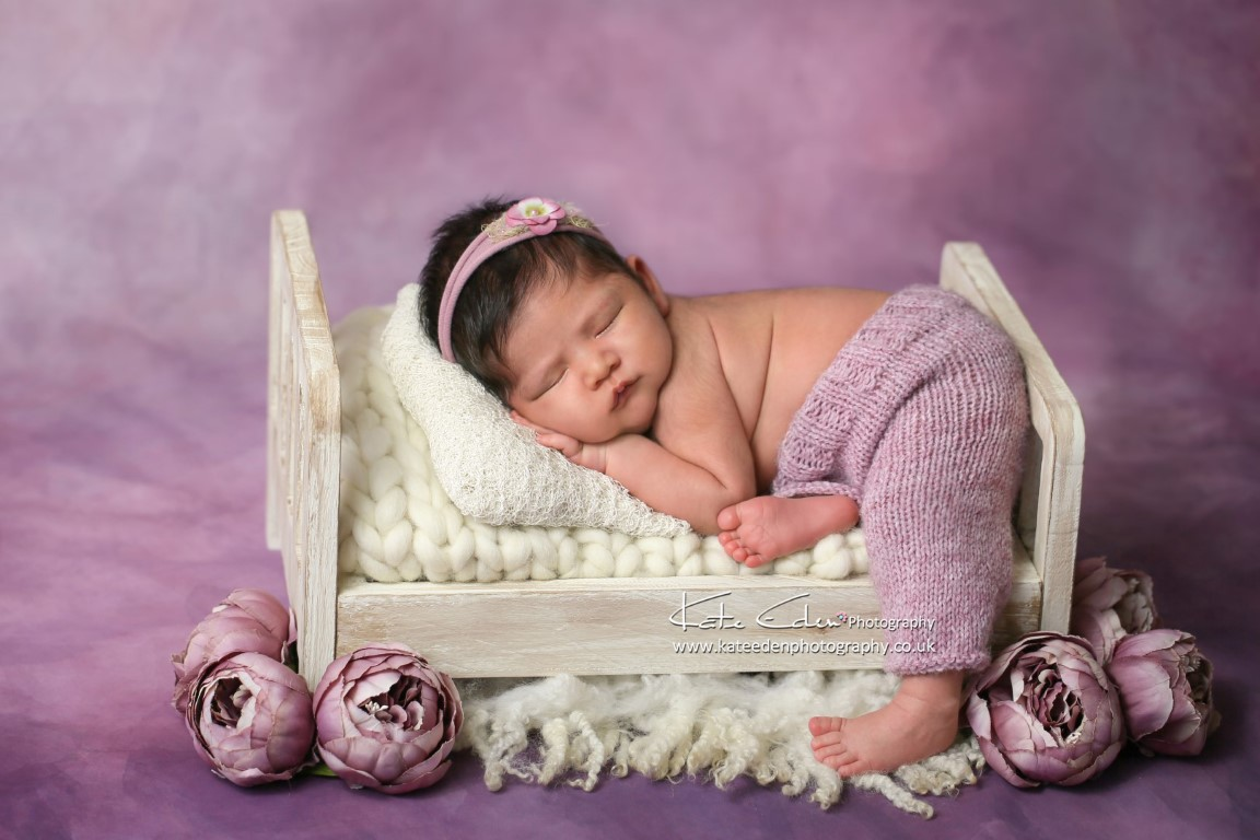 Newborn baby girl in mini bed in purple - Kate Eden Photography