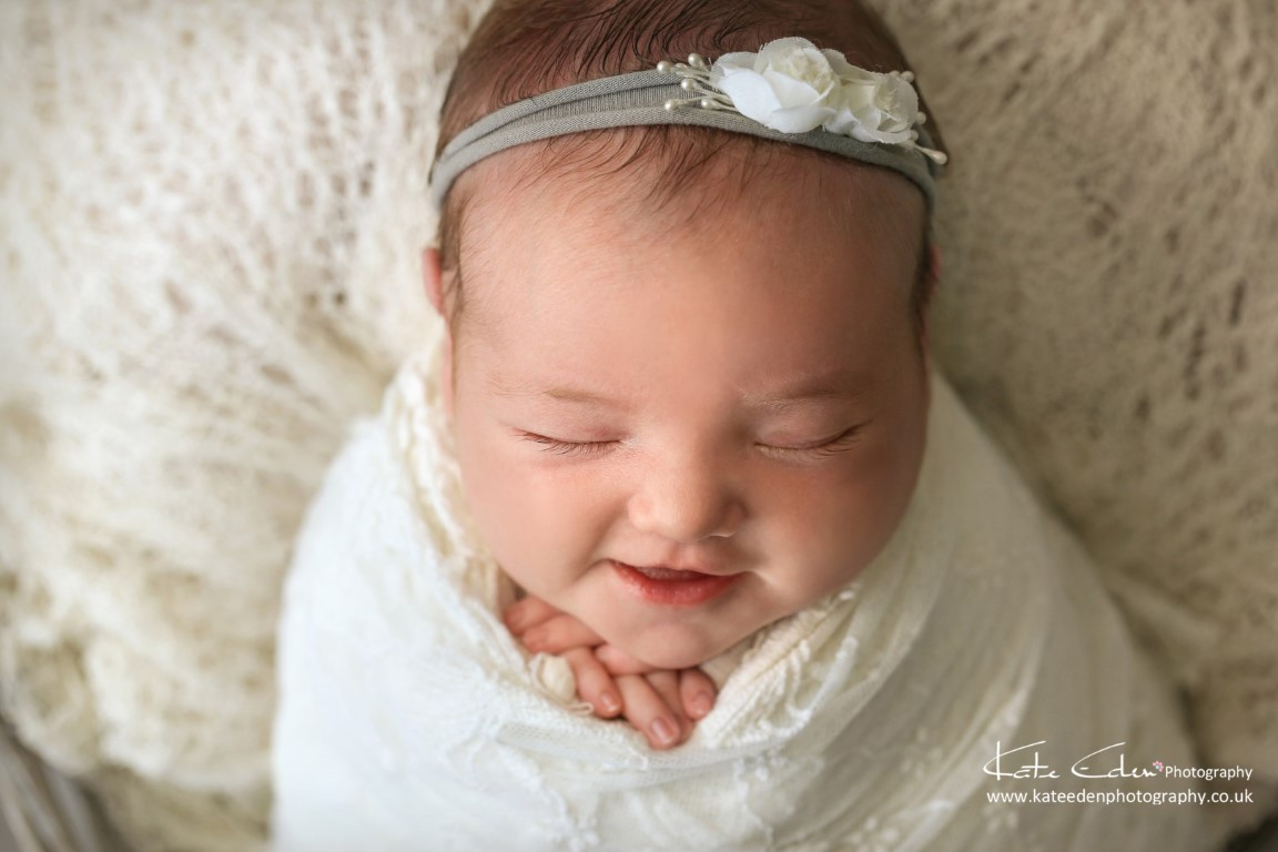 Smiling newborn baby girl - Kate Eden Photography