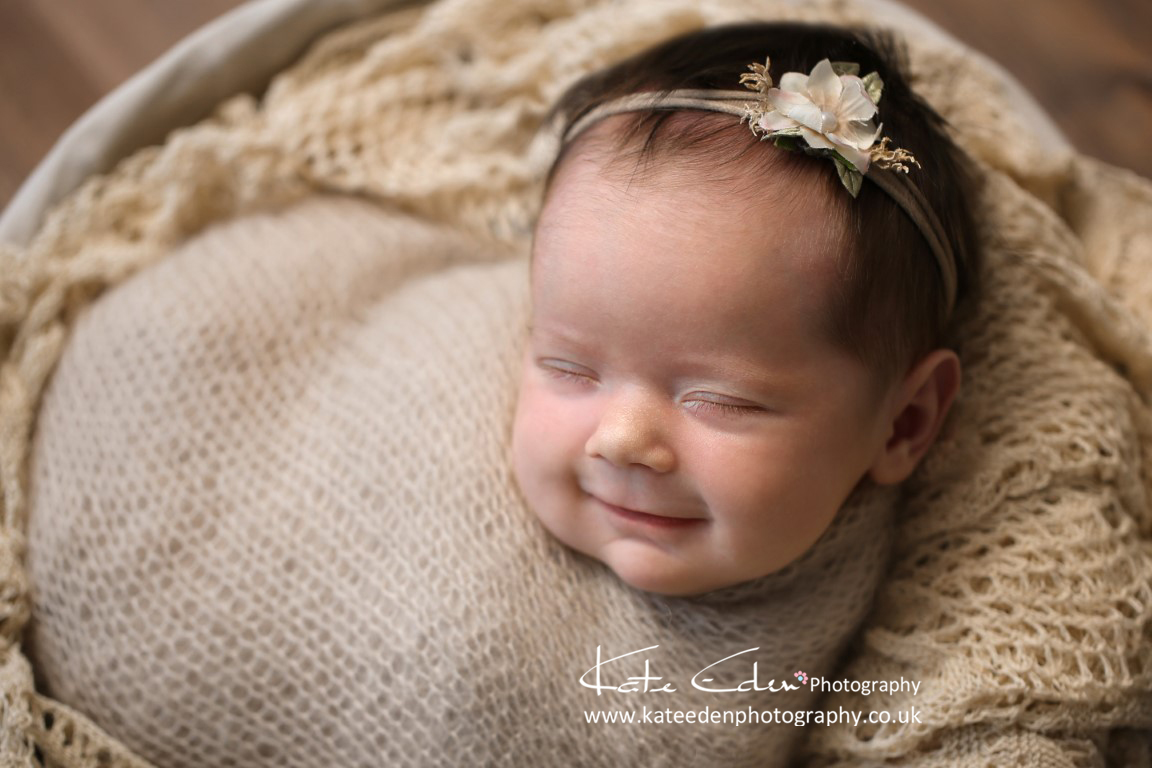A smiley newborn girl with gorgeous hair